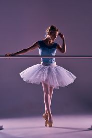 stock photo of ballet barre  - classic ballet dancer in white tutu at ballet barre on a lilac background - JPG