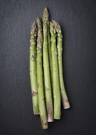 stock photo of slab  - Group of organic asparagus isolated on dark gray slate stone slab - JPG