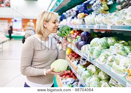 Woman Sniffs Broccoli And Holds White Cabbage In Store