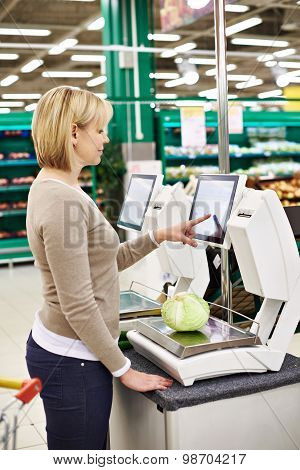Woman Weighing White Cabbage In Department Of Vegetables