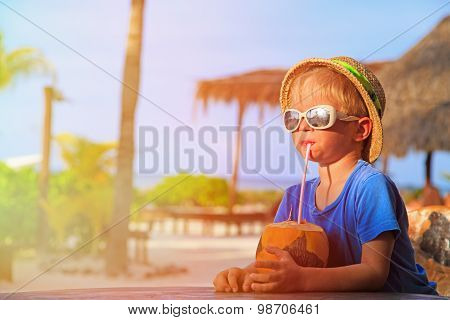 little boy drinking coconut cocktail on beach