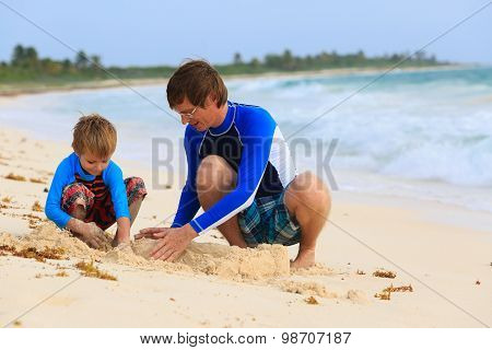 father and son building sandcastle on the beach