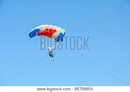 Woman -  Skydiver Against Cloudless Blue Sky