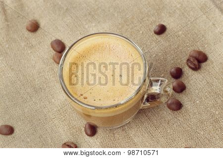 Cappuccino With Crema In A Transparent Cup On Sacking. Coffee Beans Close