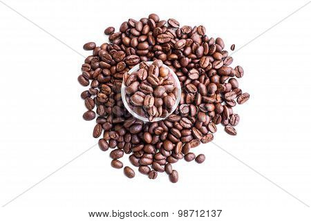 Roasted coffee beans in coffee shot glass and around