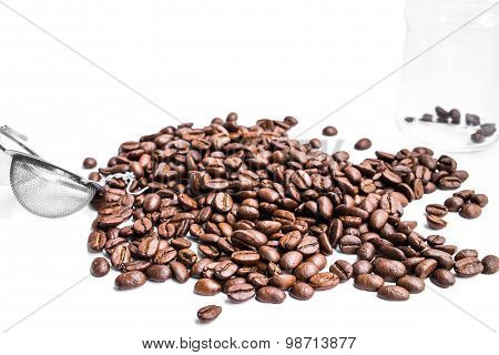 roasted coffee beans, strainer and glass jar