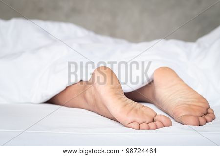 Feet Of Women On White Bedding In The Morning Time