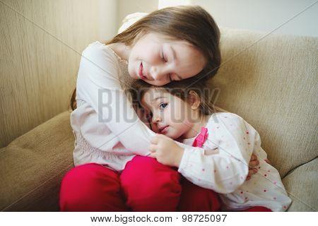girl hugging her younger sister