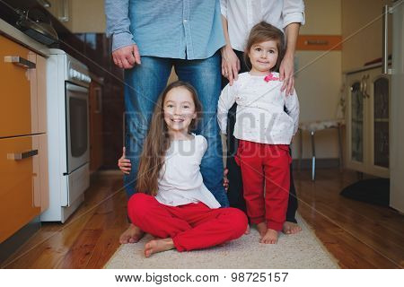girls hugging mom and dad for legs