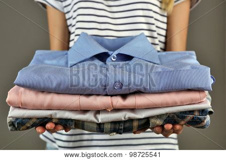 Woman holding shirts on gray background