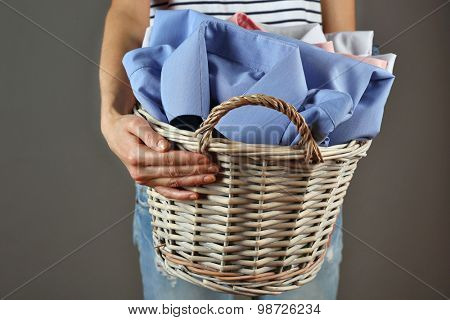 Woman holding basket with clothes on gray background