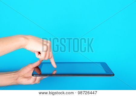 Female hands using tablet on blue background
