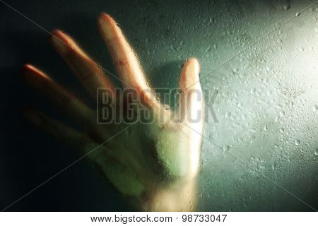 Female hand behind  wet glass, close-up