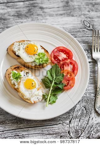 Toast With Soft Cheese And Quail Eggs On A White Plate On A Light Wooden Background