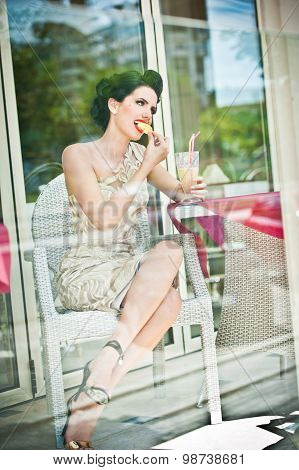Fashionable attractive young woman tasting a lemon slice in restaurant, beyond the windows