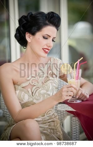 Fashionable attractive young woman in lace dress sitting in restaurant, beyond the windows