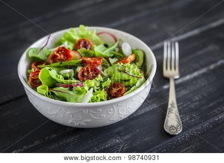 Fresh Vegetable Salad With Sun-dried Tomatoes And Balsamic Vinegar In A White Bowl On A Dark Wooden