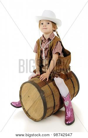 A beautiful preschool cowgirl straddling a rustic barrel as if it were a horse.  On a white background.