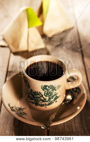 Steaming traditional oriental Chinese kopitiam style dark coffee in vintage mug and saucer with coffee beans. Fractal on the cup is generic print. Soft focus with dramatic light on wooden background.