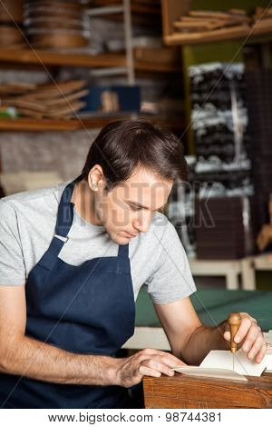 Mid adult male worker using needle to make holes on paper in factory