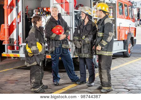 Full length portrait of confident male firefighter standing with team against truck at fire station