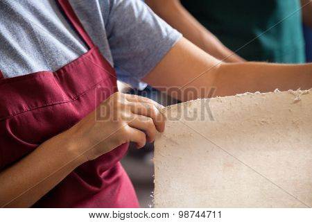 Midsection of female worker checking papers in factory