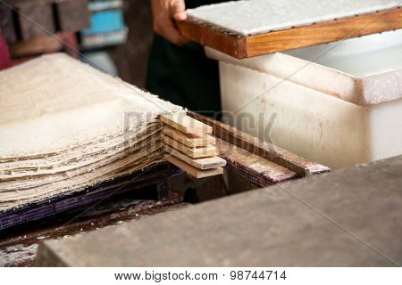 Closeup of stacked paper sheets drying in factory