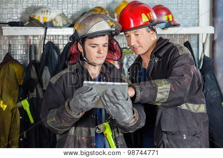 Male firefighters discussing over digital tablet at fire station