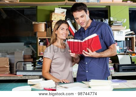 Portrait of smiling woman standing with man holding book in paper factory