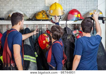 Male and female firefighters removing helmets from shelf in fire station