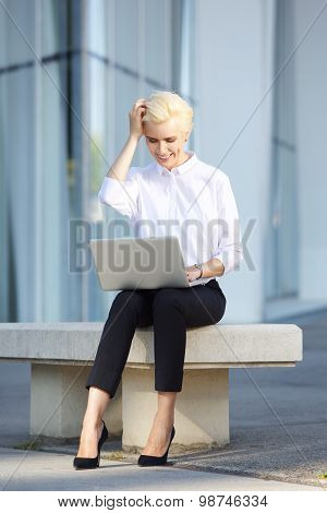Cheerful Young Business Woman Using Laptop Outside