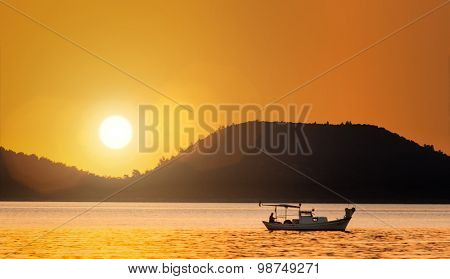 Fishing boat during sunrise over sea