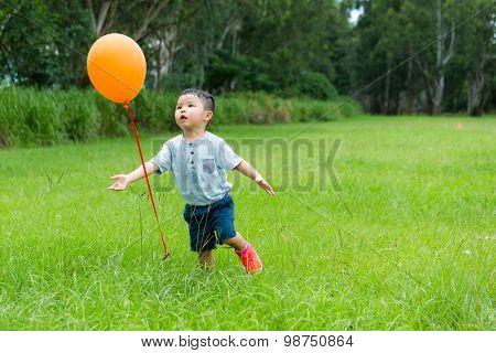 Little boy running to catch with orange balloon