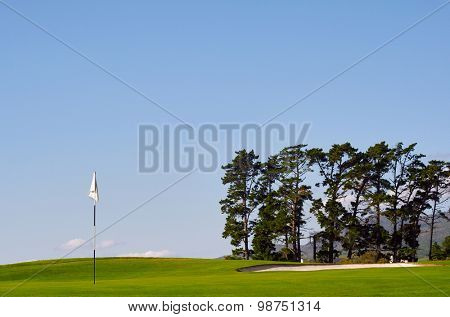 sunny golf course with pin and bunker with blue sky
