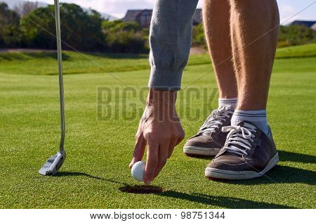 golf man taking ball out hole after making birdie