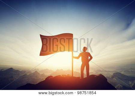 Proud man raising a flag on the peak of the mountain. Successful challenge concept, new achievement