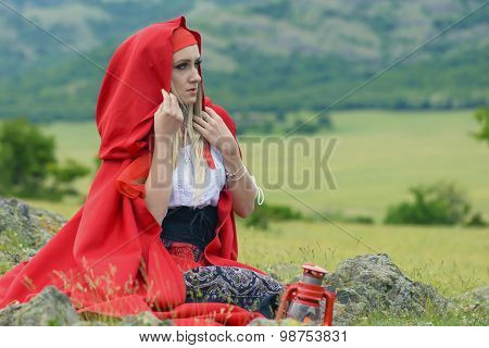 Beautiful Blonde Woman In Old-fashioned Dress And Red Cloak Sitting On The Meadow