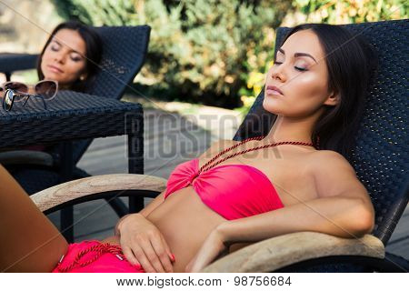 Two charming girls resting on the deckchair outdoors