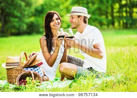 Loving couple with glasses of red wine relaxing on nature