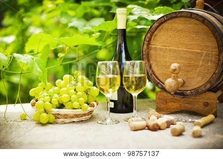 White wine, grapes and oak barrels on background of green leaves