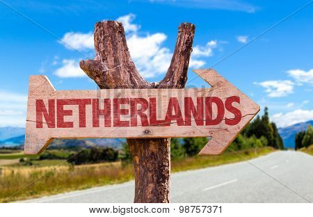 Netherlands wooden sign with road background