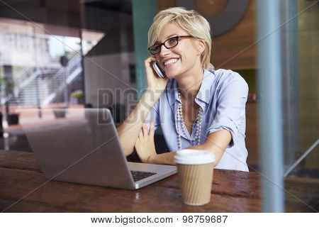 Businesswoman Using Phone Working On Laptop In Coffee Shop