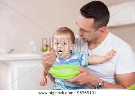Cheerful young man is caring of his child