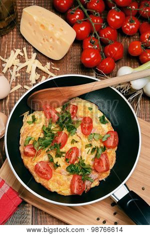 Omelette With Ham, Tomatoes And Chees On The Frying Pan.