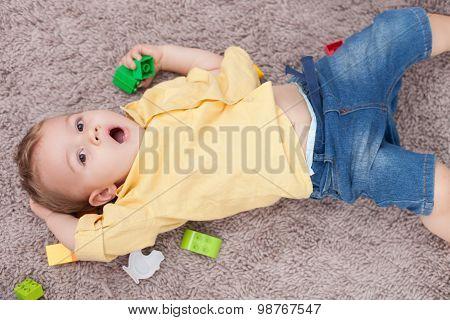 Cute small kid is making fun on flooring