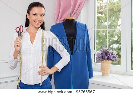 Attractive female tailor is creating new clothing