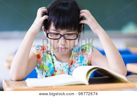 Depressed Little Girl Studing In The Classroom