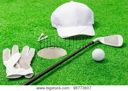 Clothing And Tools For The Game Of Golf Near The Hole On The Lawn