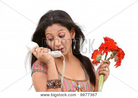 teenage Girl talking over phone holding bright red daisy flowers