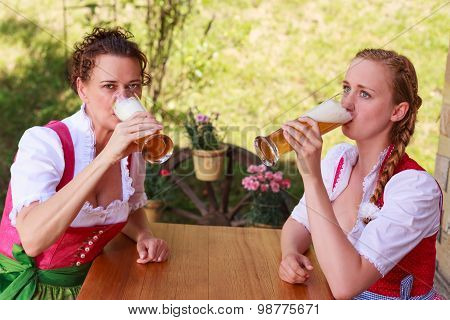 Two Attractive Bavarian Women Drinking Beer